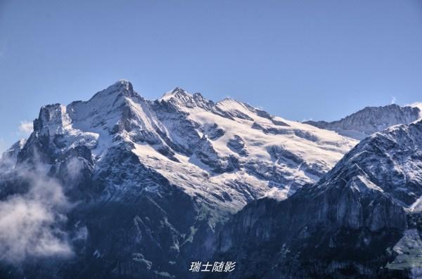 云开雾散,天际屹立着皑皑的雪山冰峰,在阳光下显得格外雄伟壮丽.